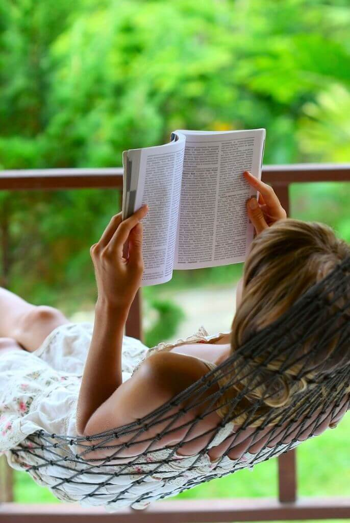 woman on a deck reading in a hammock